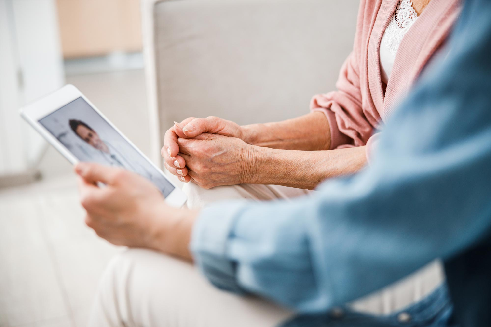 elderly female and male patient experience telemedicine with male doctor on iPad tablet